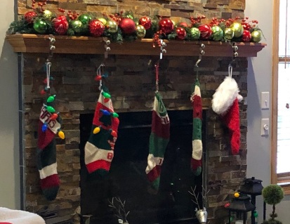 DSD's mantel, 2018, her and DSIL's stockings on left, the two I knit for DGC1 and DGC2 in middle. DGC3 is waiting me to knit his (so he has a temporary substitute).